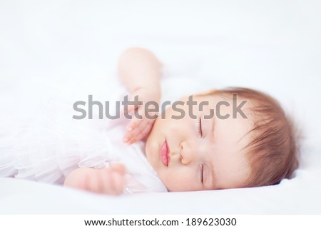 beautiful baby girl sleeping in white bed, two months old