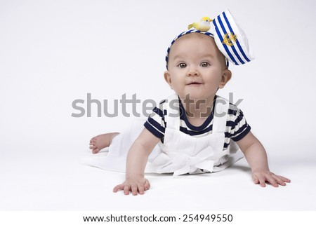 beautiful baby girl wearing a sailor outfit and smiling