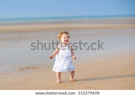 Beautiful baby girl with curly hair dressed in a white dress running on a stunning sunset beach