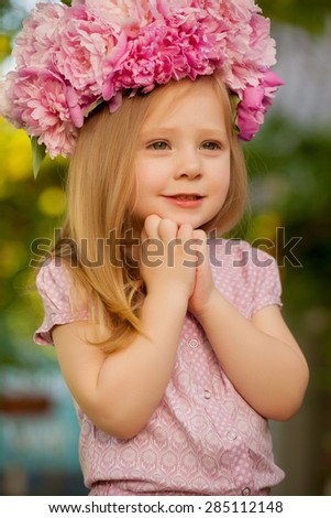 beautiful baby girl with pink flowers outdoors. Little girl 2-3 year old
