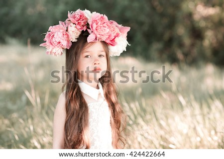 Beautiful baby girl 3-4 year old with flower hairband posing outdoors. Looking at camera. Summer season. - stock photo