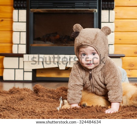 Beautiful baby in a fur hat in the interior. Winter season. Warm clothes. - stock photo