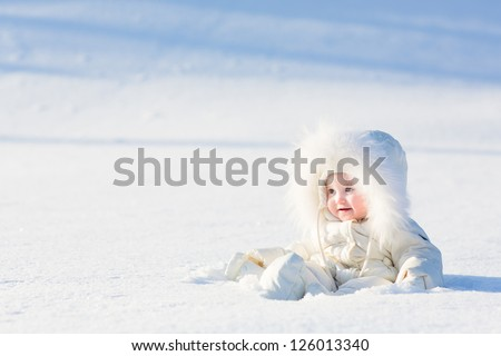 Beautiful baby in a white suit sitting in a snow field on a very sunny winter day - stock photo