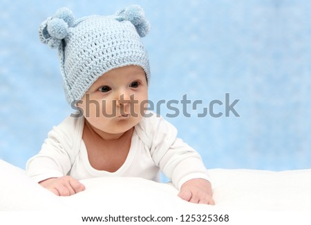 Beautiful baby in blue knitted hat - stock photo