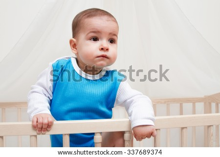 Beautiful baby in the bed on white background look at one side