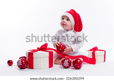 beautiful baby in the New Year's cap and white body sits among boxes of holiday gifts and Christmas balls, picture with depth of field