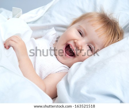 beautiful baby lying in a bed and smiling