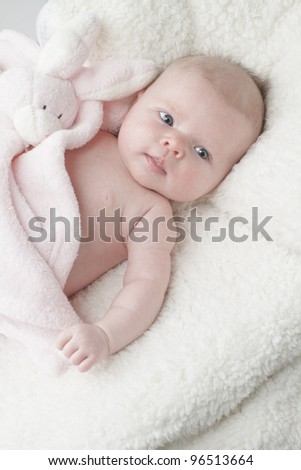 Beautiful baby lying on soft fur textured blanket with pink toy bunny rabbit, vertical layout with copy space.