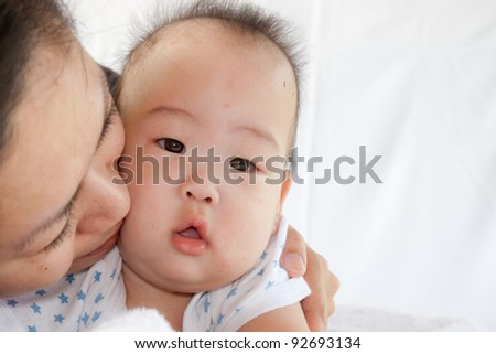 Beautiful baby of seven months old in his mothers hands
