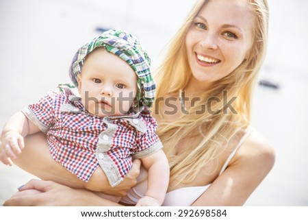 Beautiful baby on a beach with his young blond mother looking at camera Cute blondy mom Caucasian woman wear white swimsuit against water sea background Summer family travel on coast  - stock photo