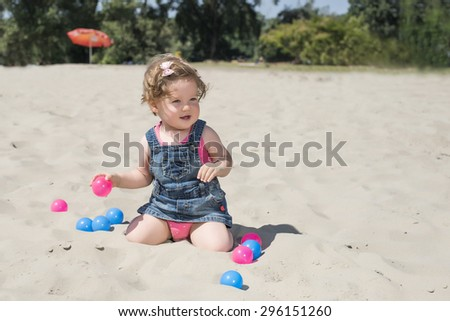 Beautiful baby playing on the beach with colorful fun balls - stock photo