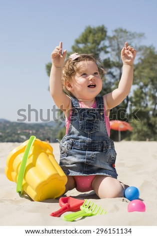Beautiful baby playing on the beach with toys - stock photo