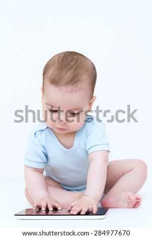 Beautiful baby playing with tablet.  - stock photo