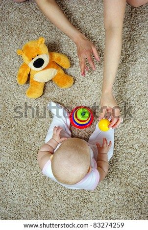 Beautiful baby playing with toys with mother indoors - stock photo