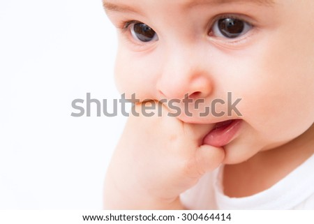 Beautiful baby portrait with hand in mouth on white background