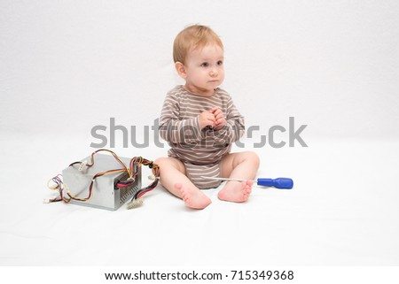 beautiful baby repairing with a screwdriver power supply from a computer on a white isolated background