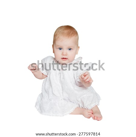 beautiful baby sits on white background, dressed in white dress, looking at camera - stock photo