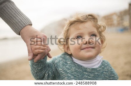 Beautiful baby thinking on beach - stock photo