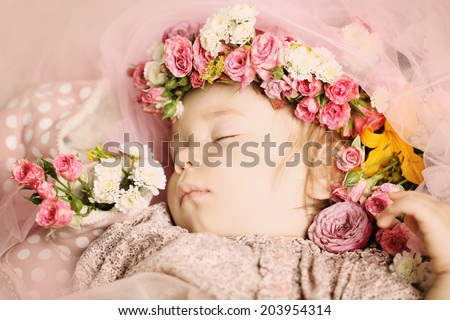Beautiful baby with flowers and accessories - stock photo