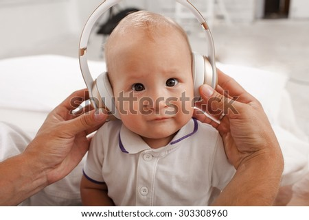 beautiful baby with headphones listening to music on white home background - stock photo