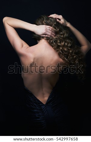 beautiful back of young woman in a black sexy dress.luxury beauty brunette Girl curly healthy hair