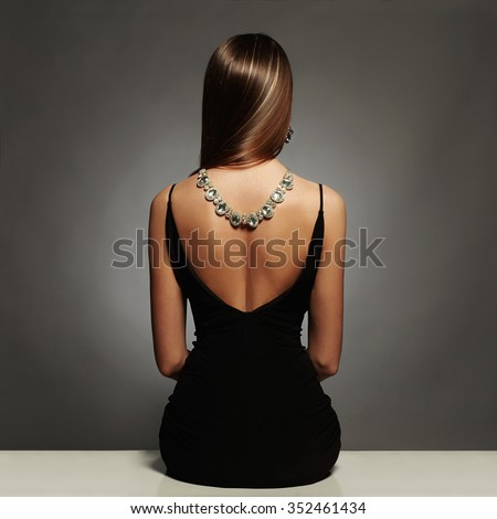 beautiful back of young woman in a black sexy dress.luxury.beauty brunette sitting girl Girl with a necklace on her back.Elegant fashion glamor photo - stock photo