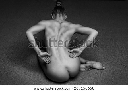 Beautiful back of young woman over dark background