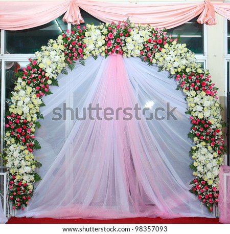 Beautiful backdrop flowers over pink and white fabric ready for wedding ceremony.