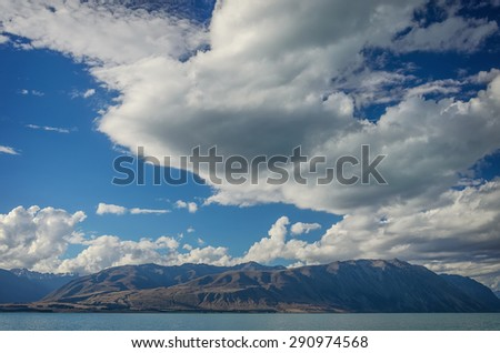 Beautiful background from The Lake Tekapo with mountains and deep blue cloudy sky. South Island, New Zealand - stock photo