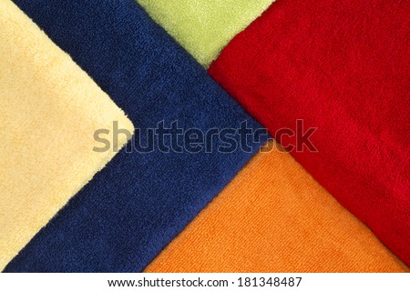 Beautiful background pattern of colorful towels neatly arranged in a striking geometric design in vibrant red, green, yellow, orange and blue