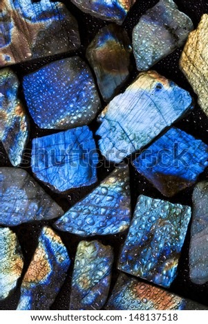 Beautiful background picture of wet natural labradorite gem stones. - stock photo