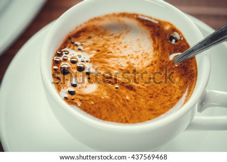 Beautiful background with a hot Cup of coffee with Crema on wooden table