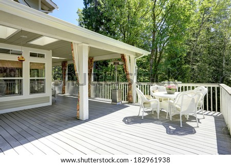 Beautiful backyard deck with white wicker table set. - stock photo