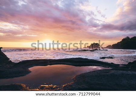 Beautiful balinese landscape. Ancient hinduism temple Tanah lot on the rock against sunset sky. Bali Island, Indonesia.