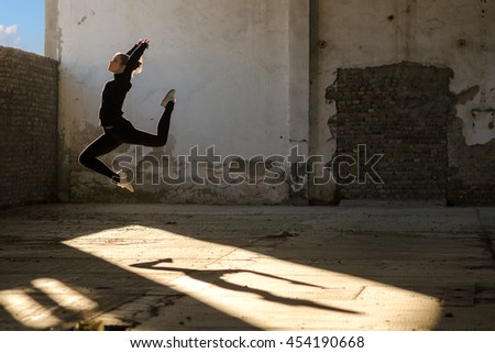 Beautiful ballerina in black track suit and sneakers jumping and dancing in abandoned building.