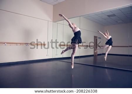 Beautiful ballerina posing in front of mirror in the dance studio - stock photo
