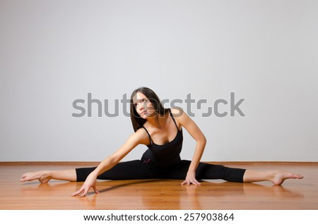 Beautiful ballet dancer performing split on the floor. - stock photo