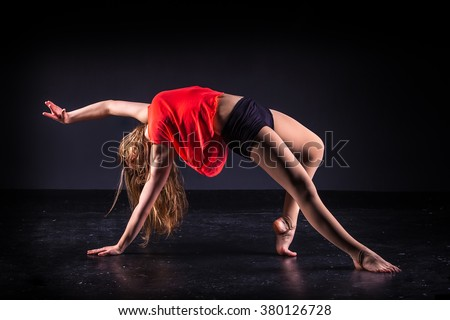 beautiful ballet dancer posing on black studio background - stock photo