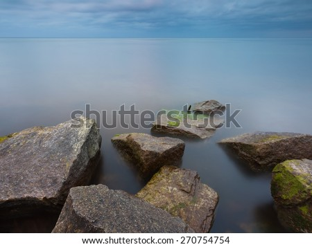 Beautiful Baltic sea landscape with stone breakwater. Tranquil long exposure landscape - stock photo