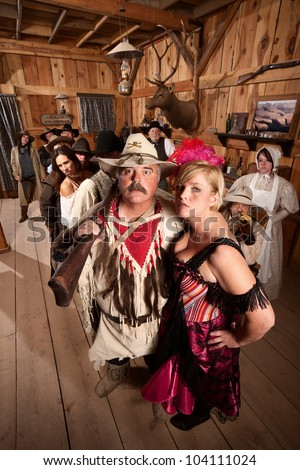 Beautiful bar maid with handsome trapper in saloon - stock photo