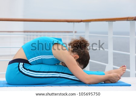 Beautiful barefoot woman dressed in blue sports suit sits on cruise liner deck and does exercise