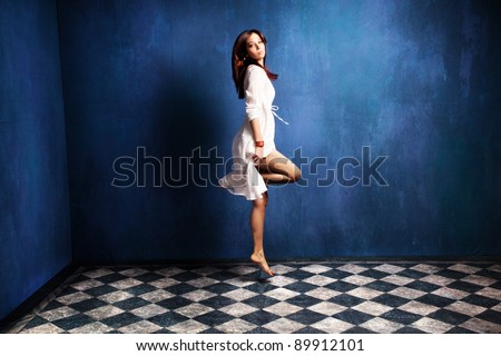 stock photo beautiful barefoot woman in white dress levitate in room 89912101 woman levitating stock images, royalty free images & vectors  at alyssarenee.co
