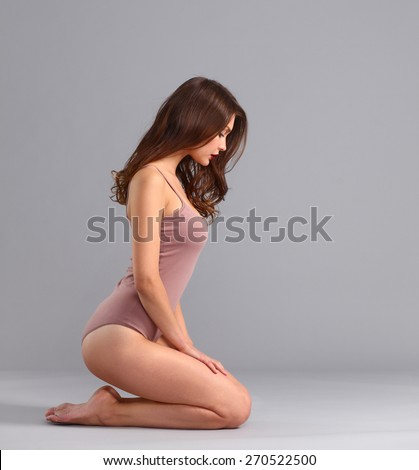 Beautiful barefoot woman sitting on the floor .