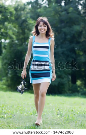 beautiful barefoot woman walking on lawn - stock photo