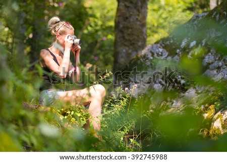 Beautiful barefooted blonde caucasian girl wearing jeans shorts an sporty black sleeveless t-shirt, sitting on a forest clearing, taking photos with retro camera. Square composition. - stock photo