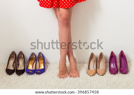 Beautiful barefooted girl is standing in a row with high heeled shoes, cropped - stock photo