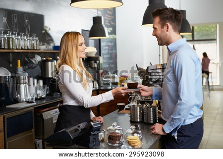Beautiful barista giving coffee to client - stock photo