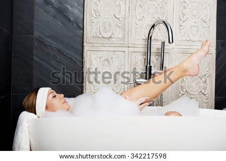 Beautiful bathing woman relaxing in bathtub with leg up. - stock photo