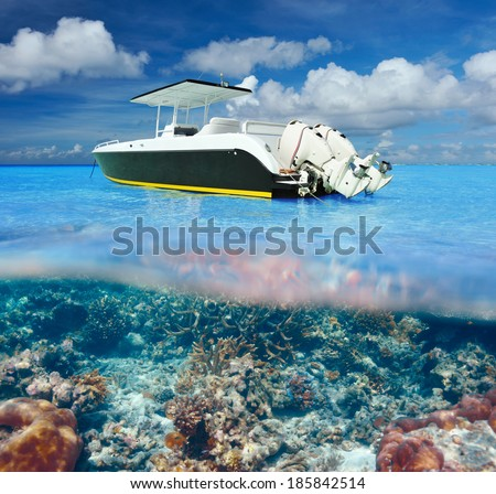 Beautiful beach and motor boat with coral reef bottom underwater and above water split view - stock photo