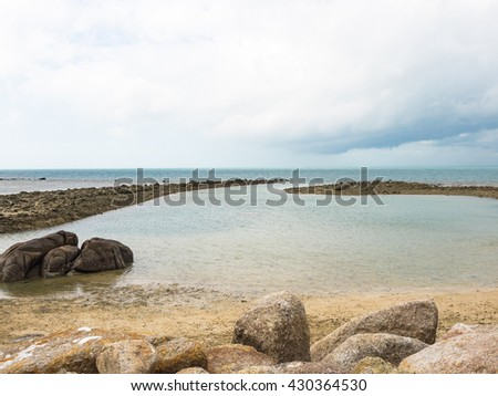 Beautiful beach and rocks lead way to ocean and blue sky white clouds. Tranquil clam sea with sand and sunshine in summer season. - stock photo